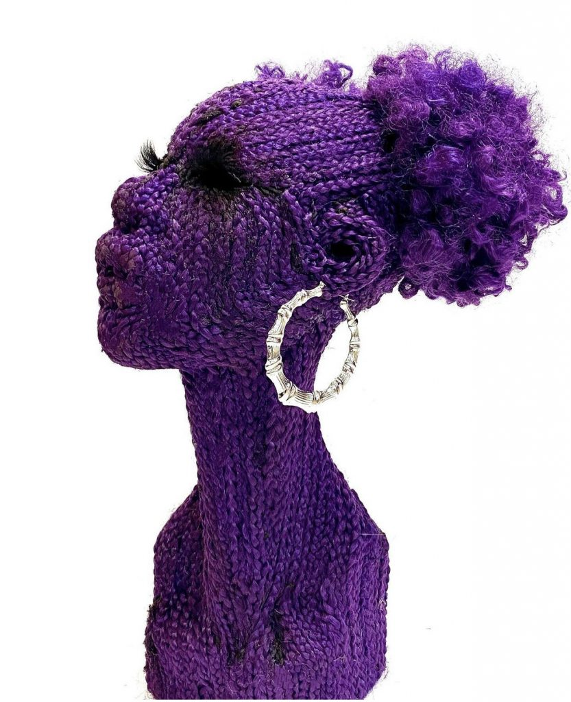 Purple sculpture of Black woman's head and neck adorned with silver bamboo earrings, afro puffs, and thick eyelashes. The sculpture is made from synthetic braids.